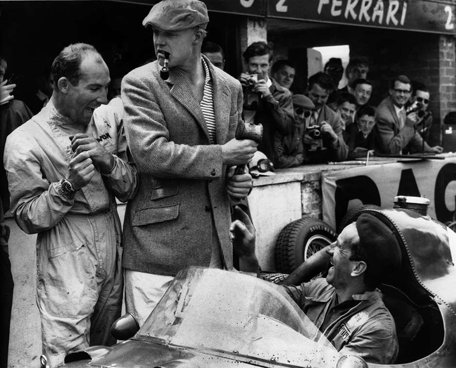 Silverstone, England. 17th - 19th July 1958. Stirling Moss (Vanwall VW10), retired, shares a joke with Mike Hawthorn (Ferrari Dino 246), 7th position, in the pits with a mechanic, portrait.  World Copyright: LAT Photographic. Ref: B/W Print.