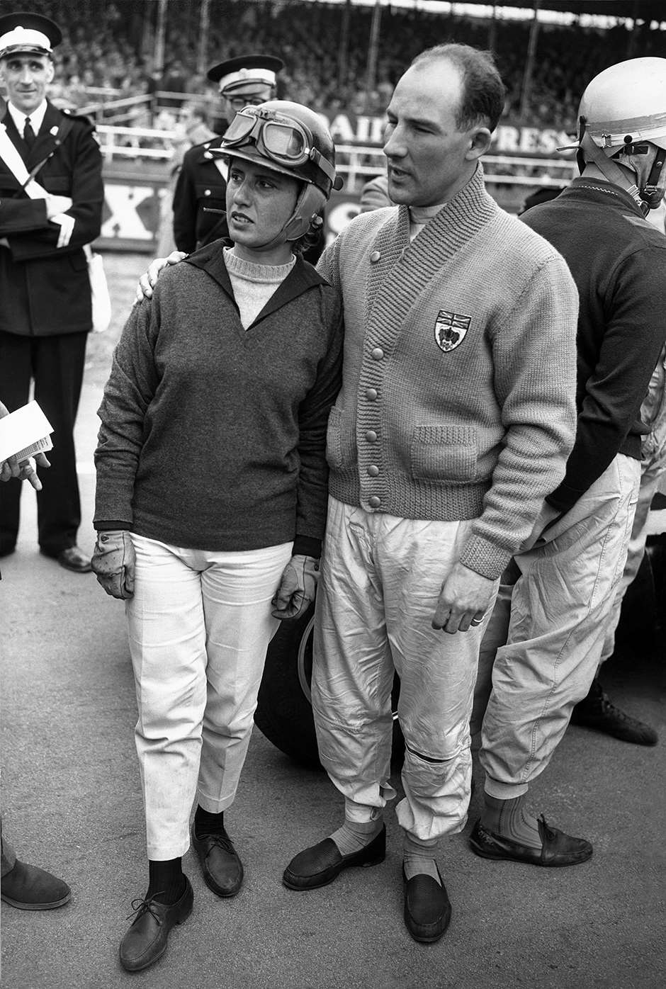 Silverstone, England. 2nd May 1959. Stirling Moss (BRM 25), retired, puts a consoling arm around the shoulders of Maria Teresa De Filippis (Maserati 250F), retired, whose Maserati was in trouble on the starting grid, portrait. World Copyright: LAT Photographic. Ref:  B/W Print.