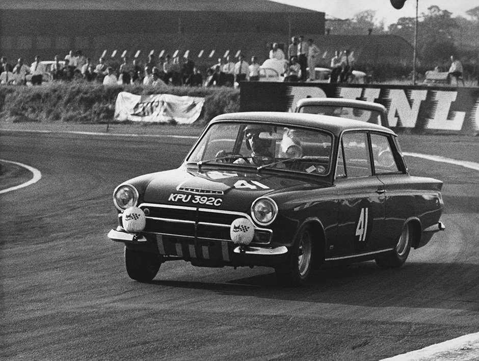1965 European Touring Car Championship. Snetterton 500 Kms, Snetterton, Norfolk, England. 15th August 1965. Rd 7. John Whitmore (Ford Lotus Cortina), 1st position, action. World Copyright: LAT Photographic. Ref: B/W Print.