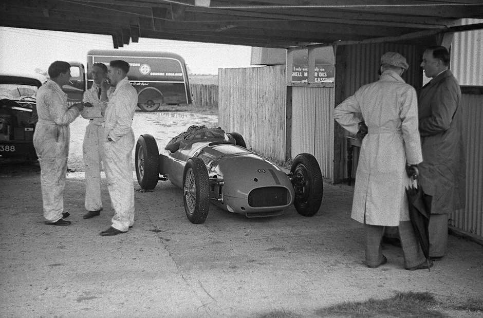 Practice period shot of the new BRM V16 - chassis 'No 2' - in shelter, team transporter in the paddock beyond.