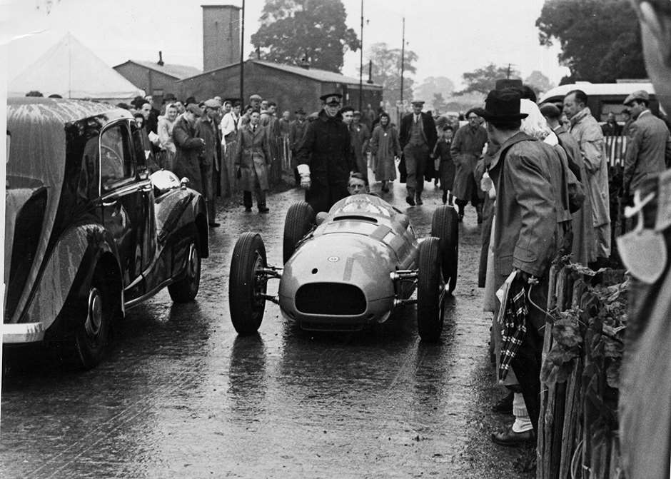 BRM Chief Mechanic Ken Richardson taxying BRM V16 'No 2' through the public area behind the grandstands